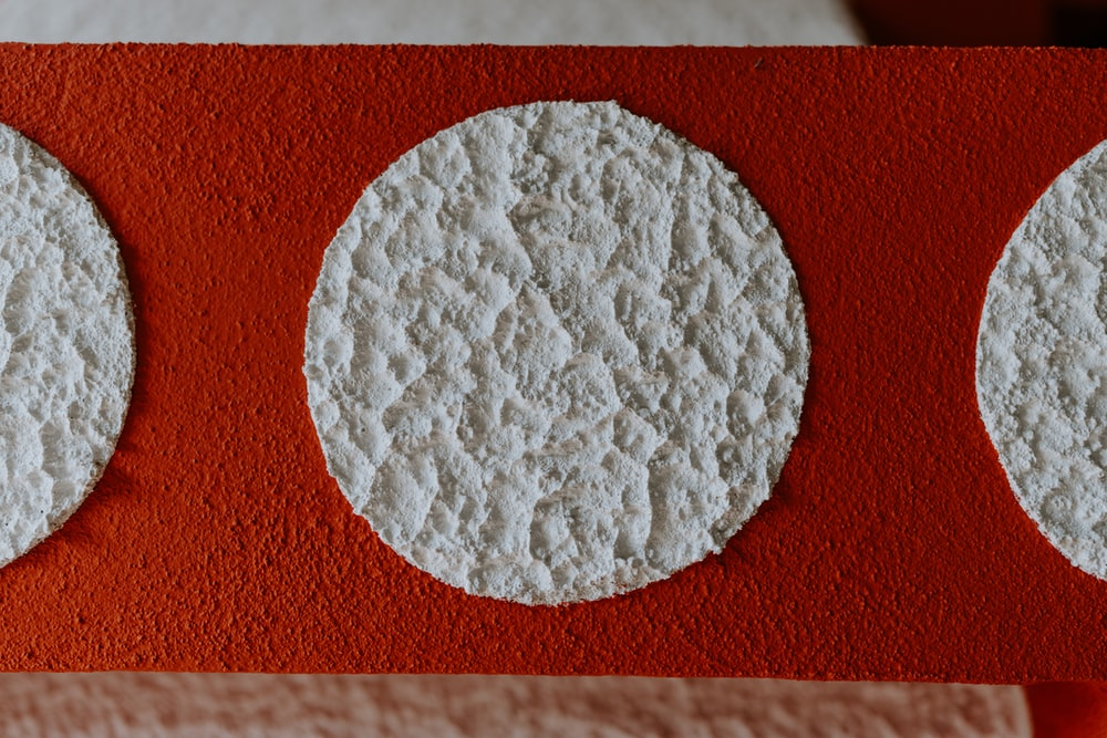 white round ornament on red textile