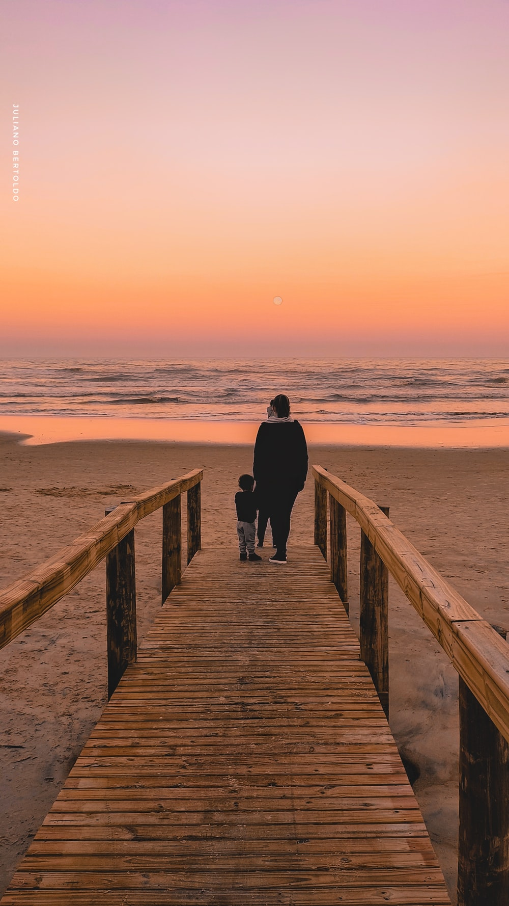 man in black jacket standing on brown wooden dock during sunset