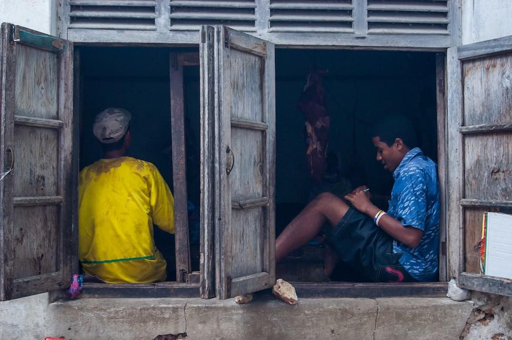 man in blue crew neck t-shirt sitting on yellow wooden door