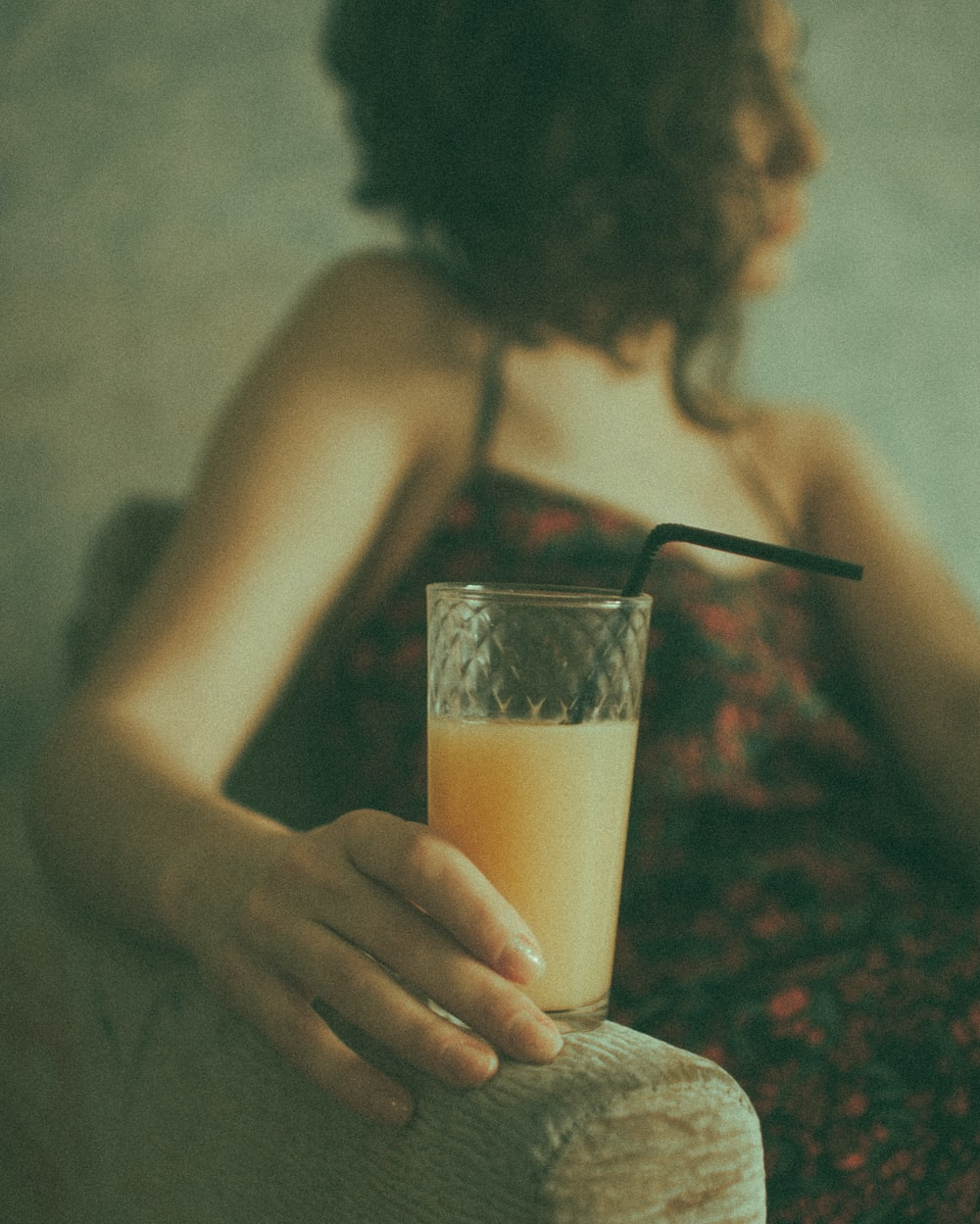 woman holding clear drinking glass with brown liquid