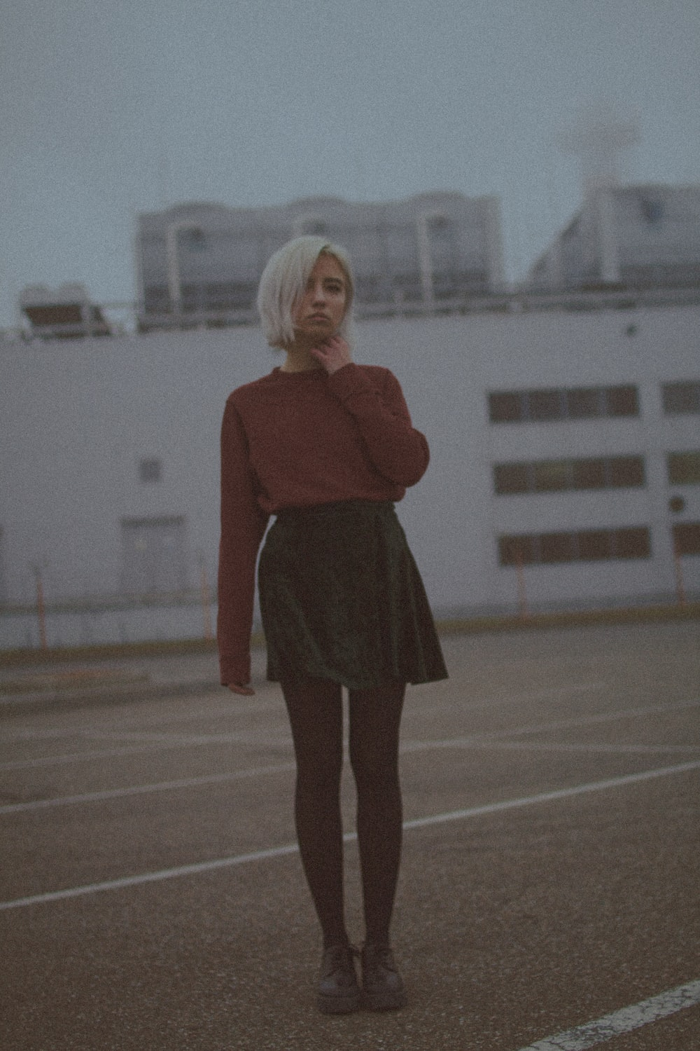 woman in red long sleeve shirt and black skirt standing on brown field during daytime