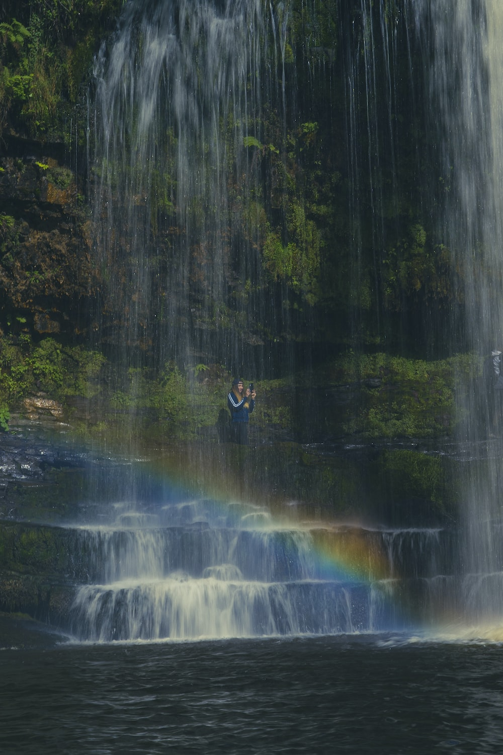 man in black jacket sitting on rock in front of waterfalls during daytime