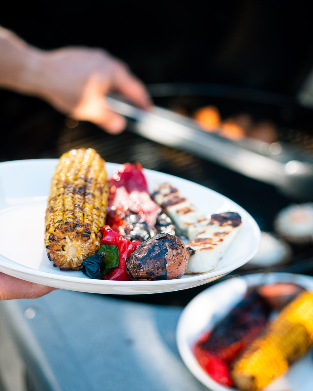 person holding stainless steel fork with grilled meat on white ceramic plate