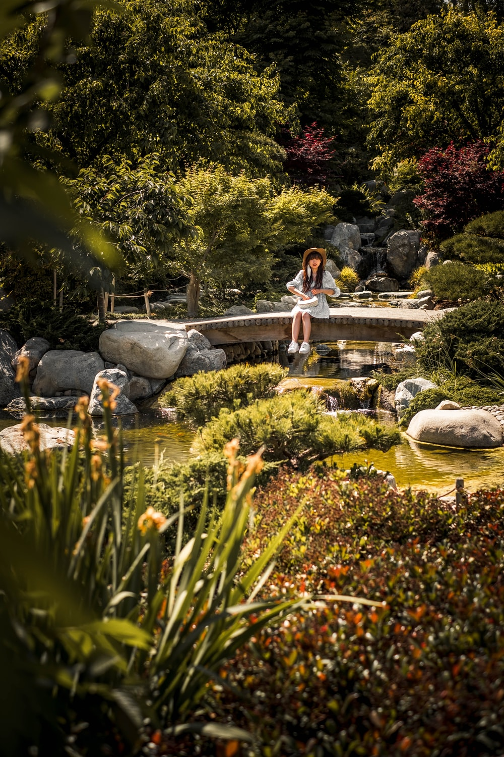 woman in blue dress sitting on rock in front of water fountain