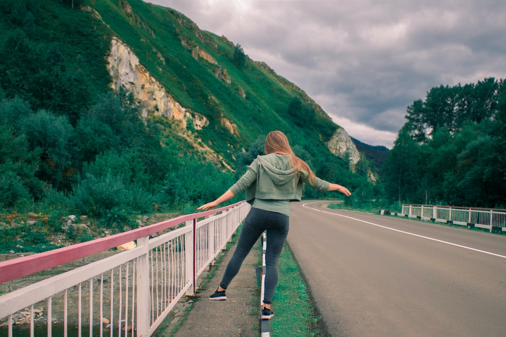 woman in gray jacket and blue denim jeans walking on gray concrete bridge during daytime