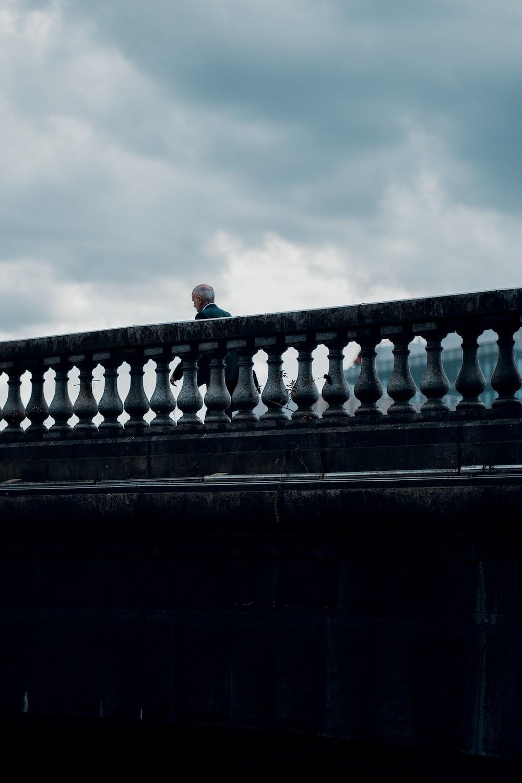 man in black jacket standing on concrete bridge during daytime
