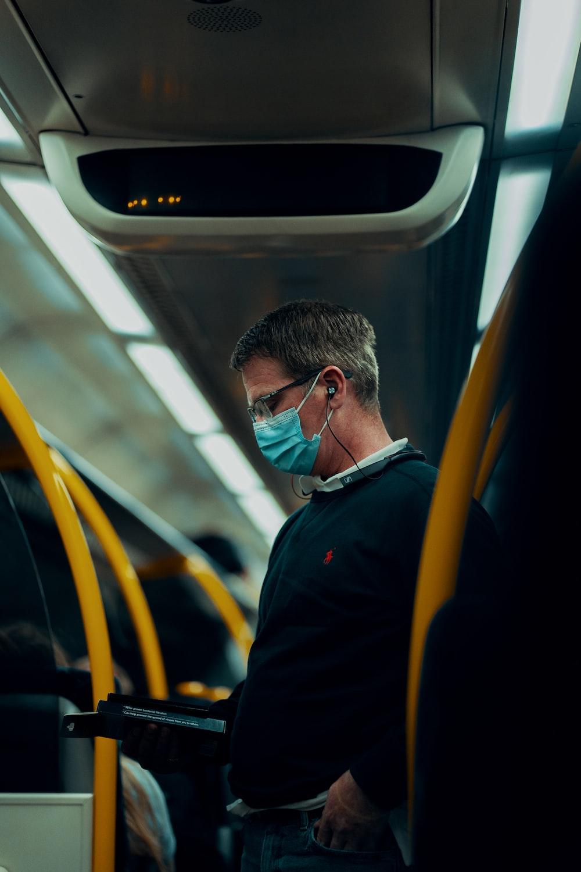 man in black jacket wearing sunglasses sitting inside train