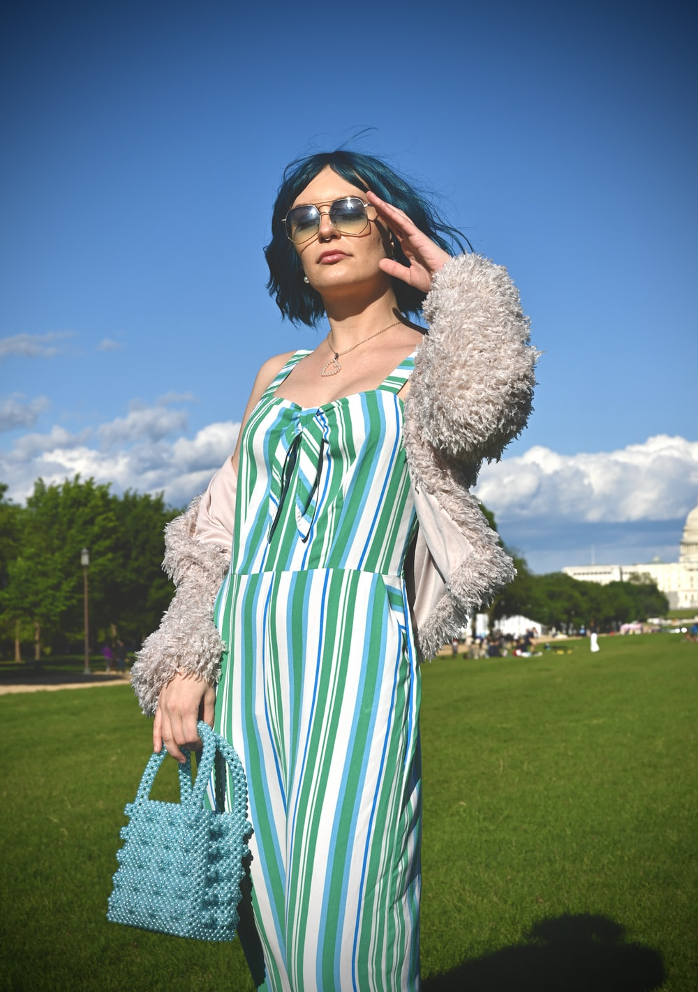 woman in white and green dress wearing black sunglasses standing on green grass field during daytime