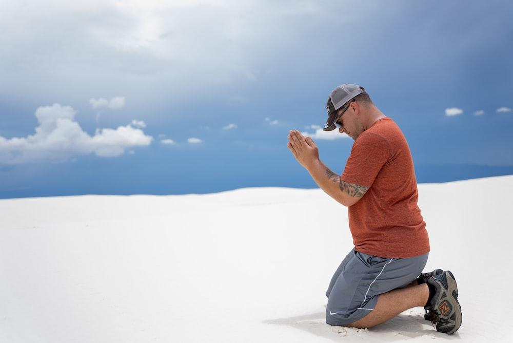 man in orange polo shirt and blue denim shorts sitting on white sand during daytime