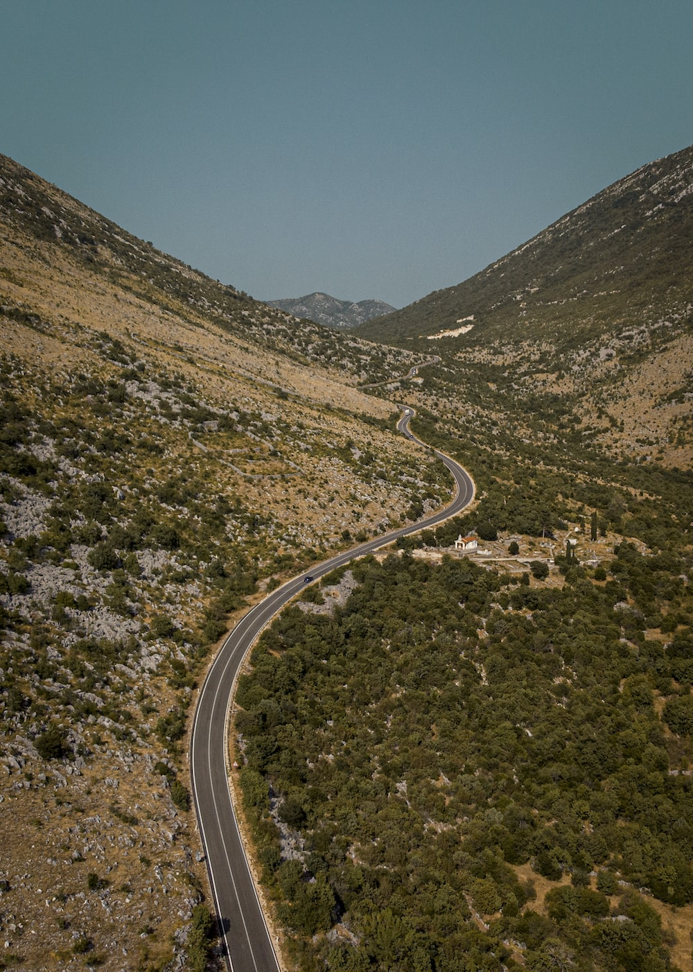 aerial view of road between green trees and mountains during daytime