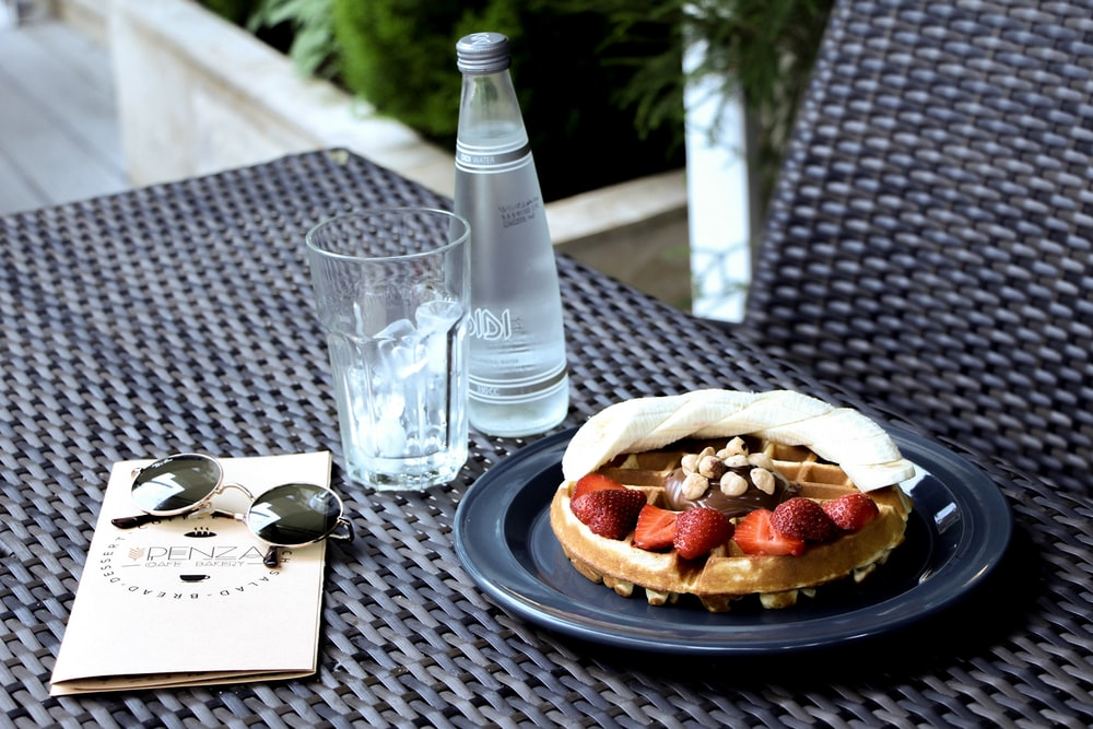 sliced bread on white ceramic plate beside clear drinking glass on black table