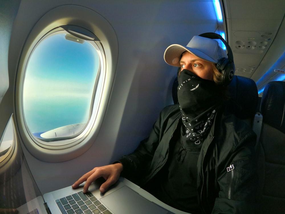 man in black jacket and black cap using macbook air