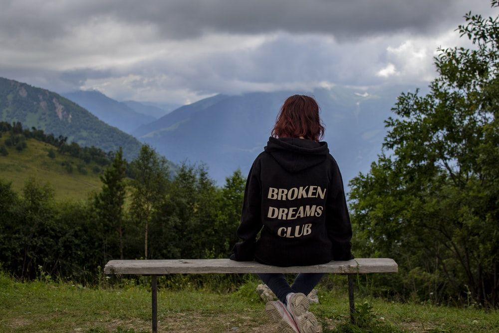 woman in black and white hoodie sitting on brown wooden bench looking at mountains during daytime