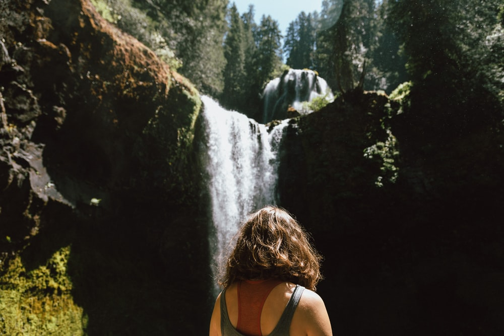 woman in black tank top standing near waterfalls during daytime