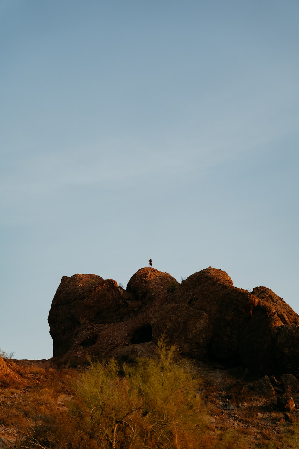 person standing on brown rock formation under white sky during daytime