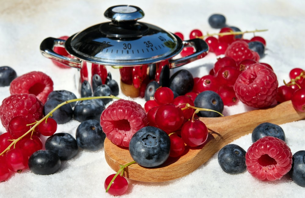 black and red berries on brown wooden spoon