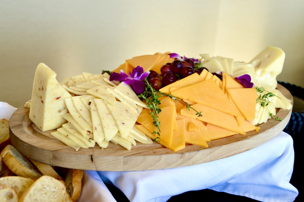 sliced cheese on brown wooden chopping board
