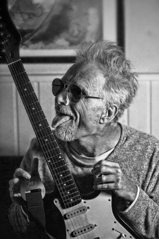 man in black sunglasses playing guitar