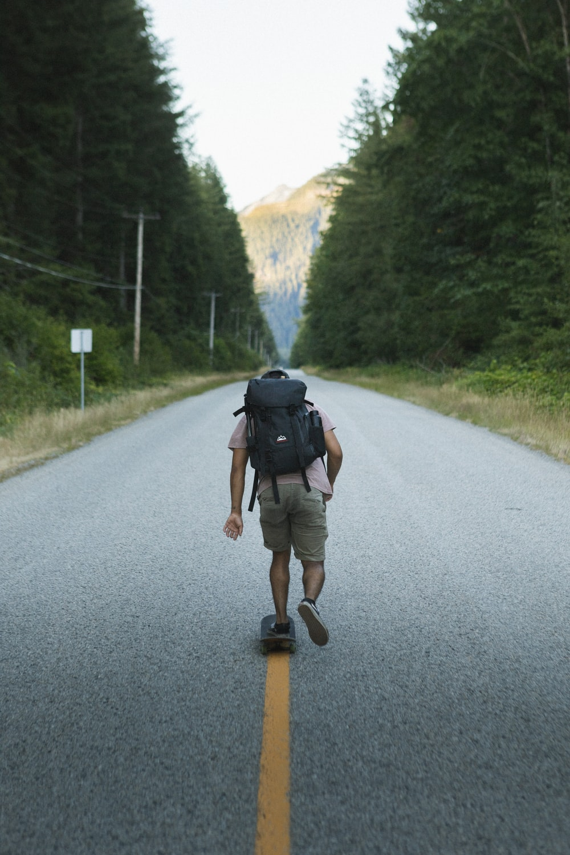 man in black jacket and gray pants walking on gray asphalt road during daytime