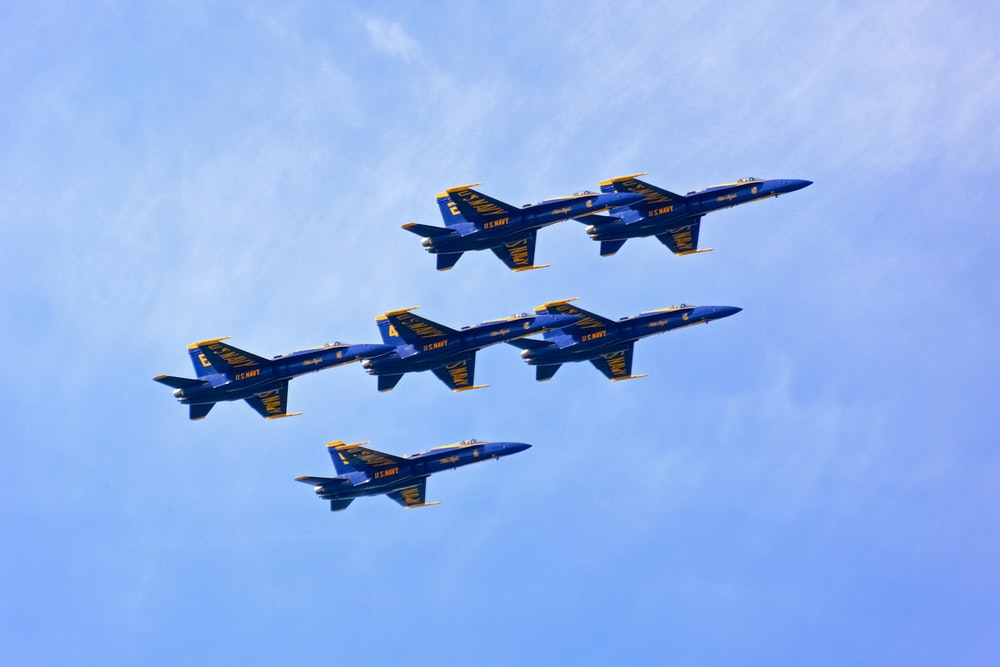 four fighter planes flying in the sky during daytime