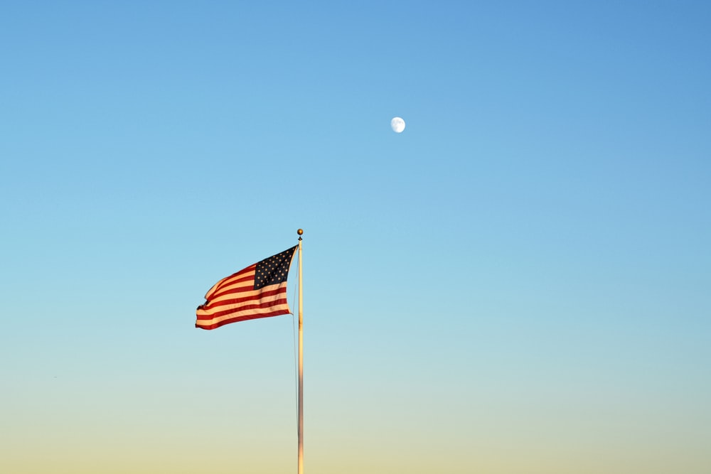 us a flag on pole during daytime