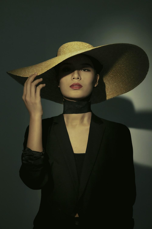woman in black blazer wearing brown straw hat