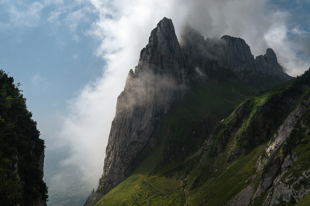 green and black mountain under white clouds during daytime