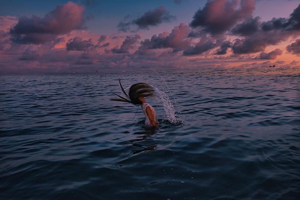 woman in black bikini swimming on sea during sunset