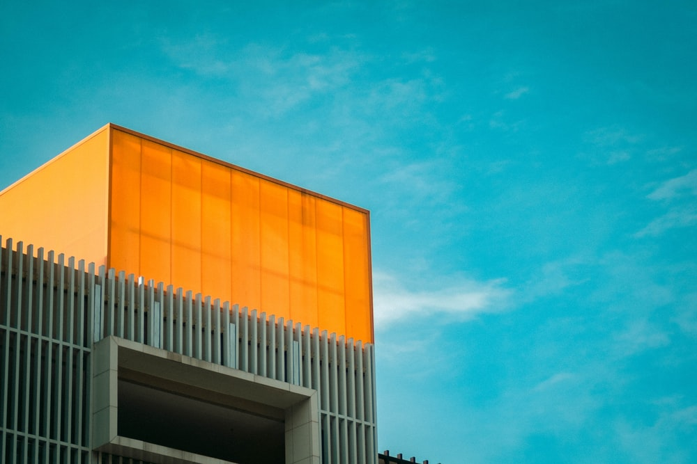 orange and white concrete building under blue sky during daytime