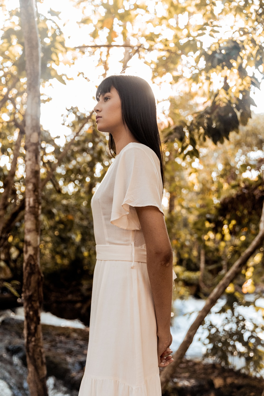 woman in white dress standing near trees during daytime