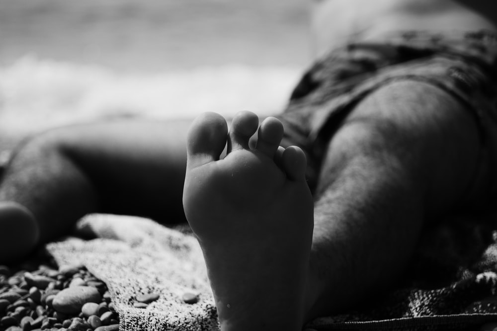 grayscale photo of persons feet on beach
