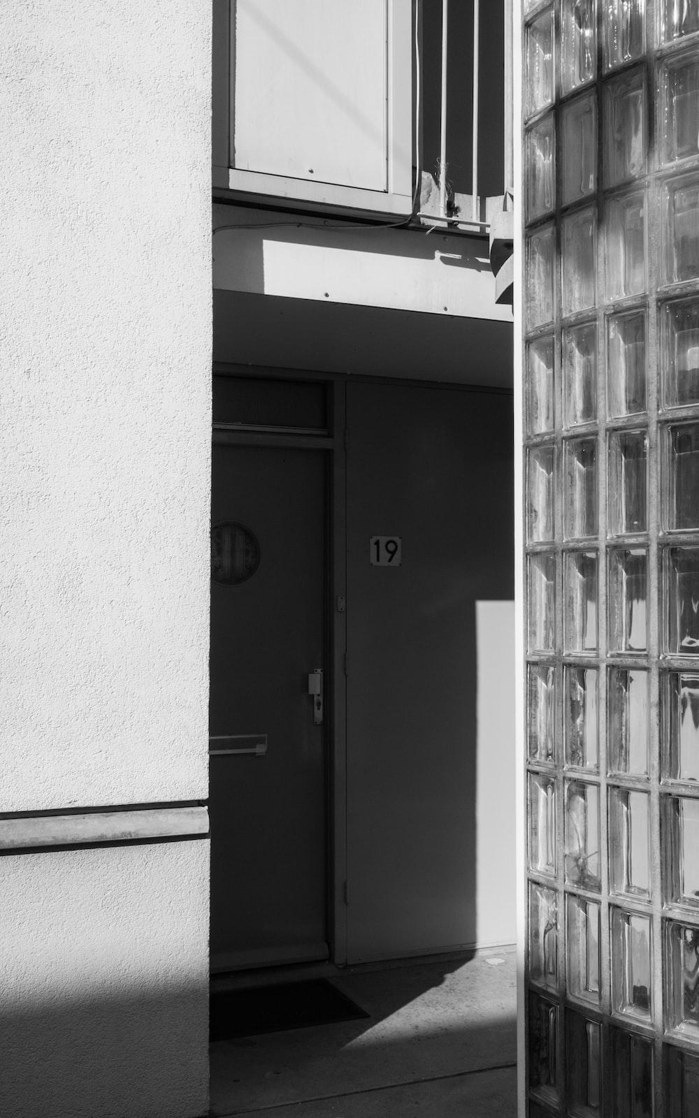 black wooden door beside white wall