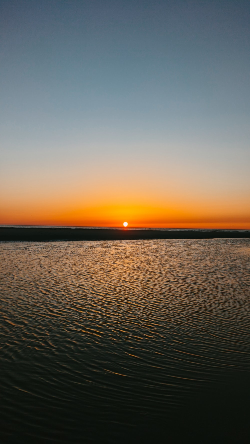 calm sea under orange sky during sunset