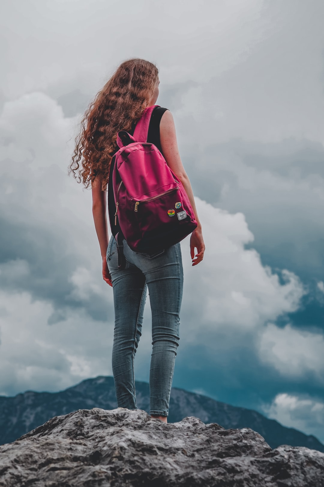 woman in red tank top and blue denim jeans with black and red backpack