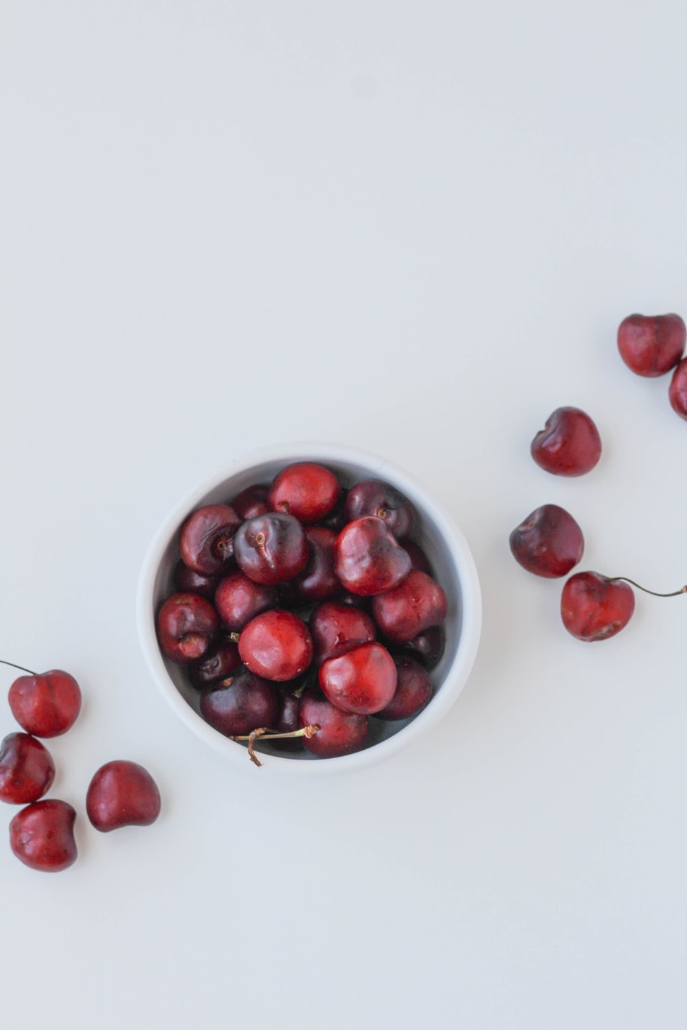 red round fruits on white surface