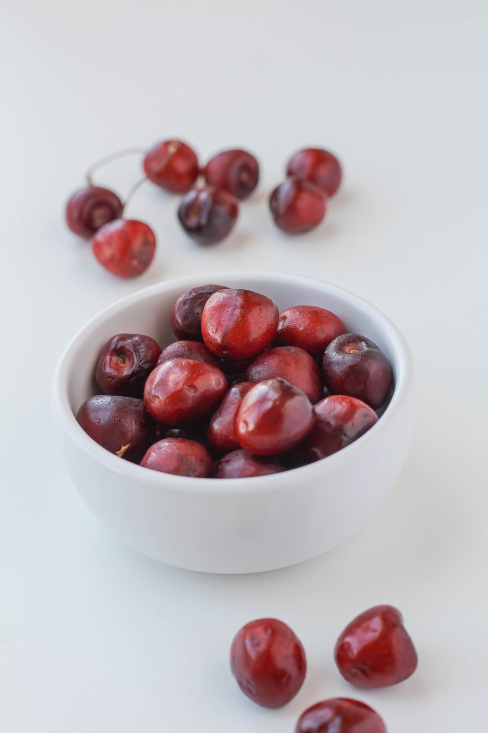 red round fruits in white ceramic bowl