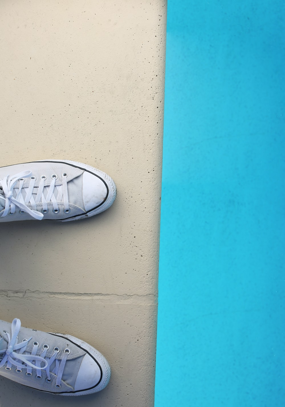 person wearing white low top sneakers
