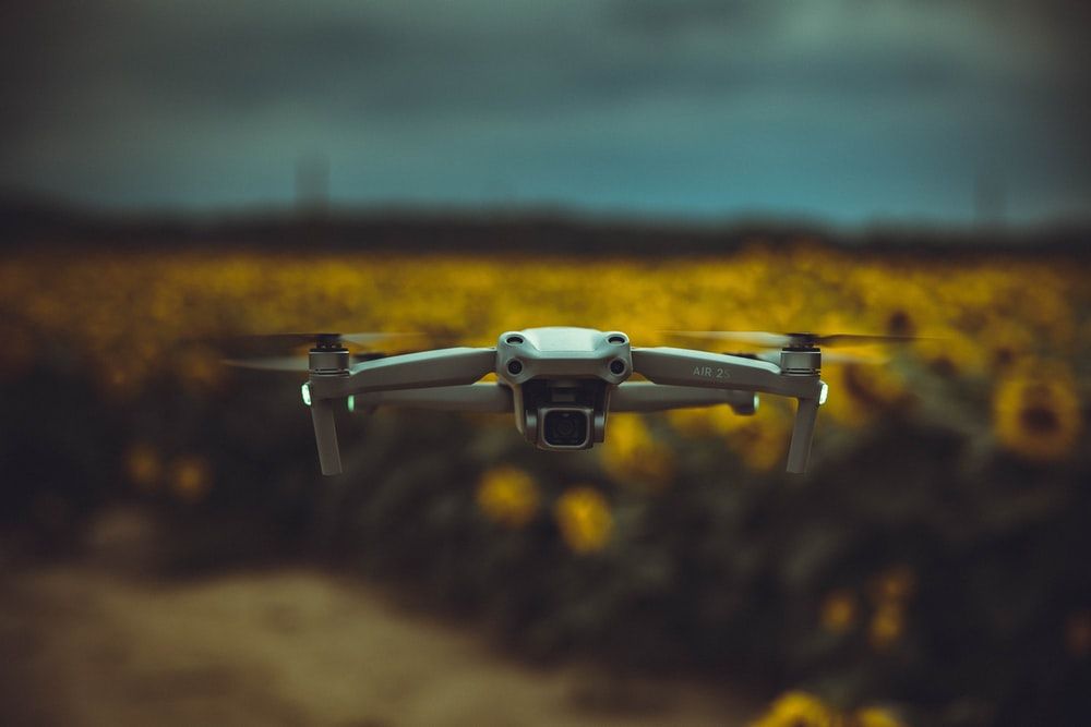 white drone flying over green grass field during daytime
