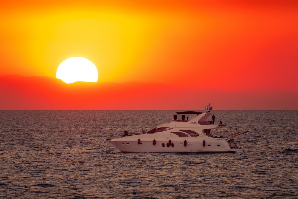 white yacht on sea during sunset