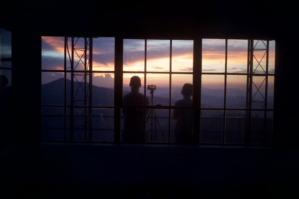 silhouette of people standing on window during sunset
