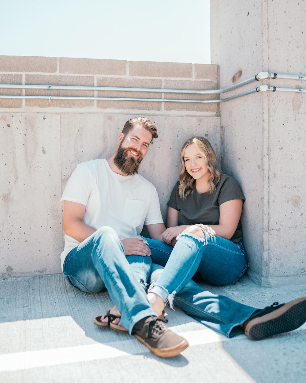 man in white crew neck t-shirt sitting beside woman in blue denim jeans