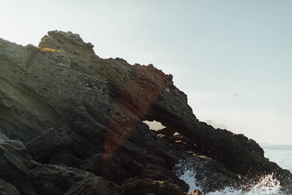brown rock formation on sea during daytime