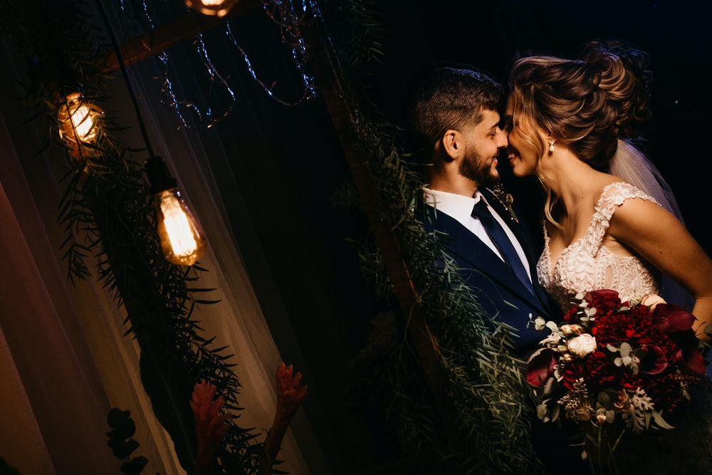 man in black suit kissing woman in white dress