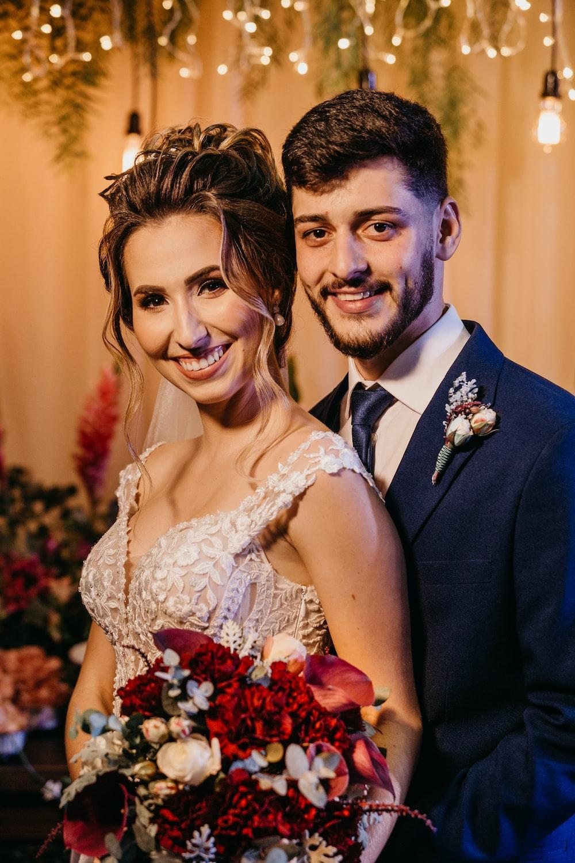 man in black suit jacket beside woman in white floral wedding dress