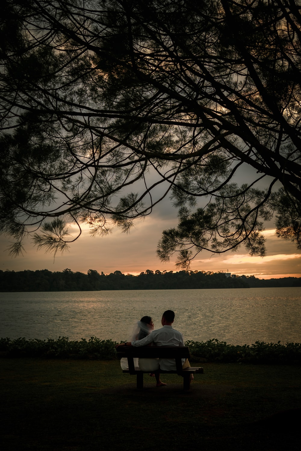 man sitting on bench near body of water during sunset
