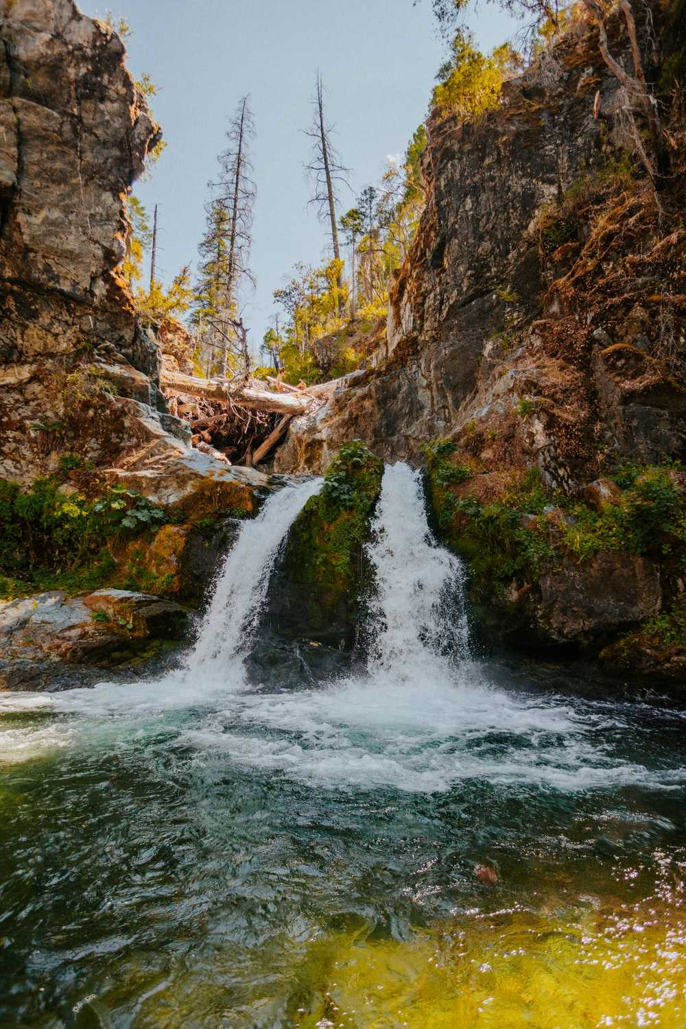 water falls between brown rock formation during daytime