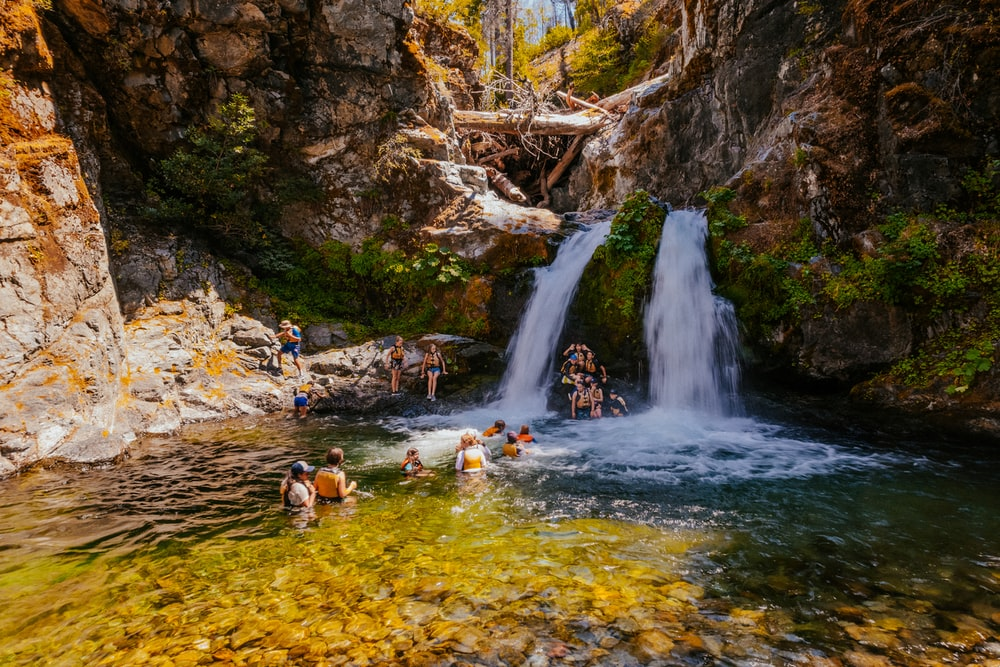 people in water falls during daytime