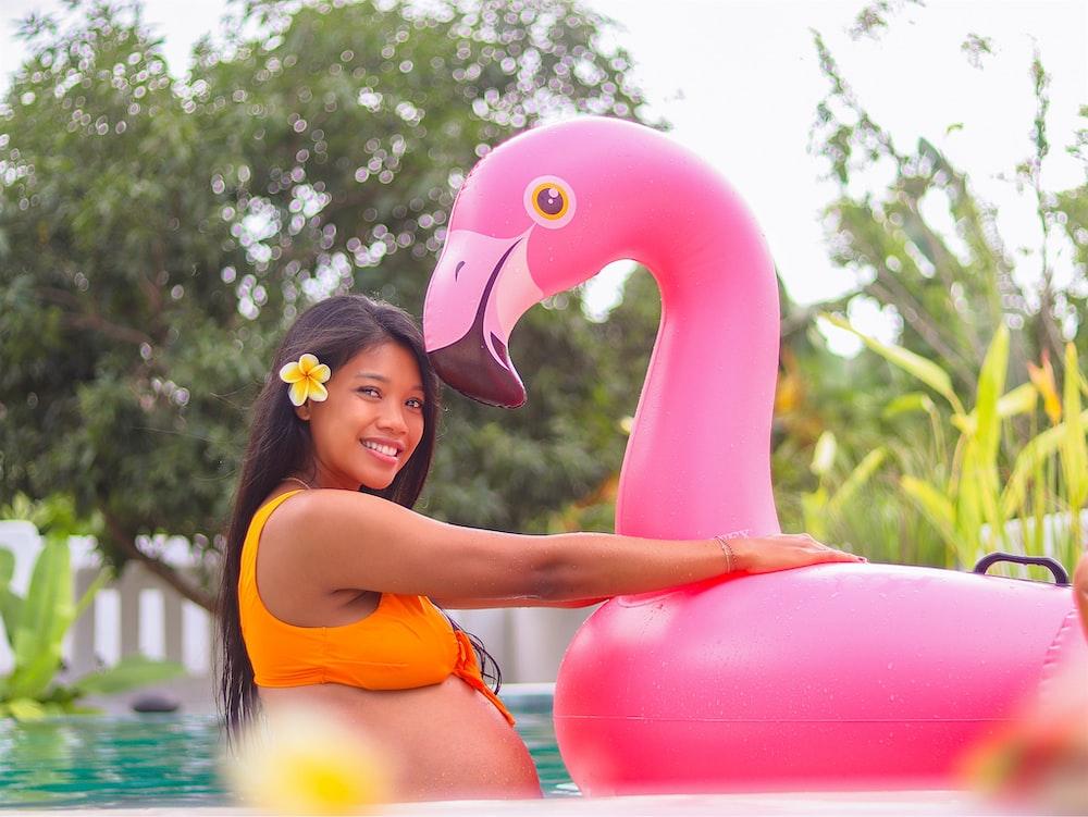 woman in orange bikini top holding pink inflatable flamingo