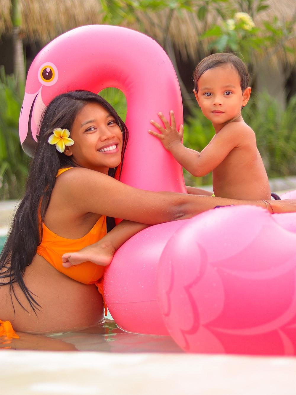 girl in orange bikini top holding pink inflatable balloons