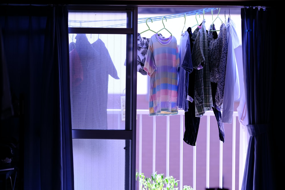 white and blue clothes hanging on white wooden door